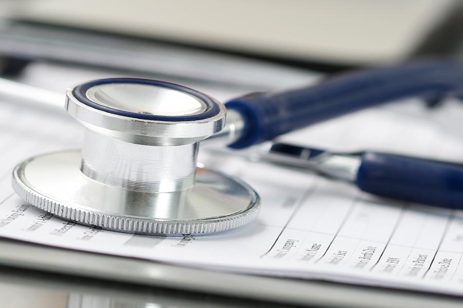 Stethoscope head lying on medical form