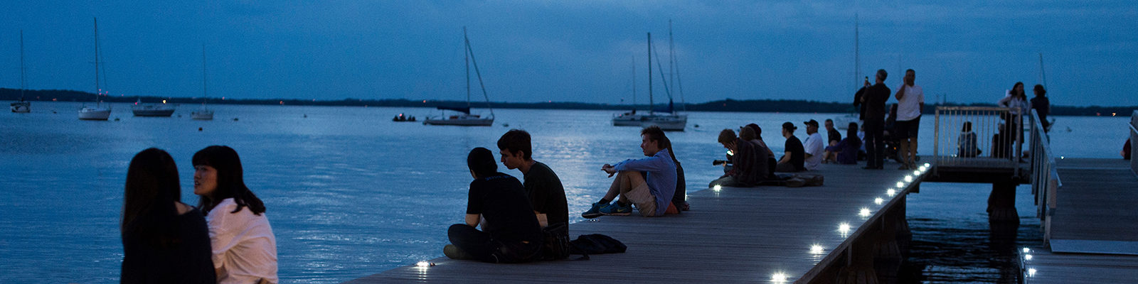 As dusk falls to nighttime, people relax on the Goodspeed Family Pier and take in a post-sunset view of the Memorial Union Terrace and Lake Mendota shoreline at the University of Wisconsin-Madison during a summer evening on June 14, 2014. (Photo by Jeff Miller/UW-Madison)