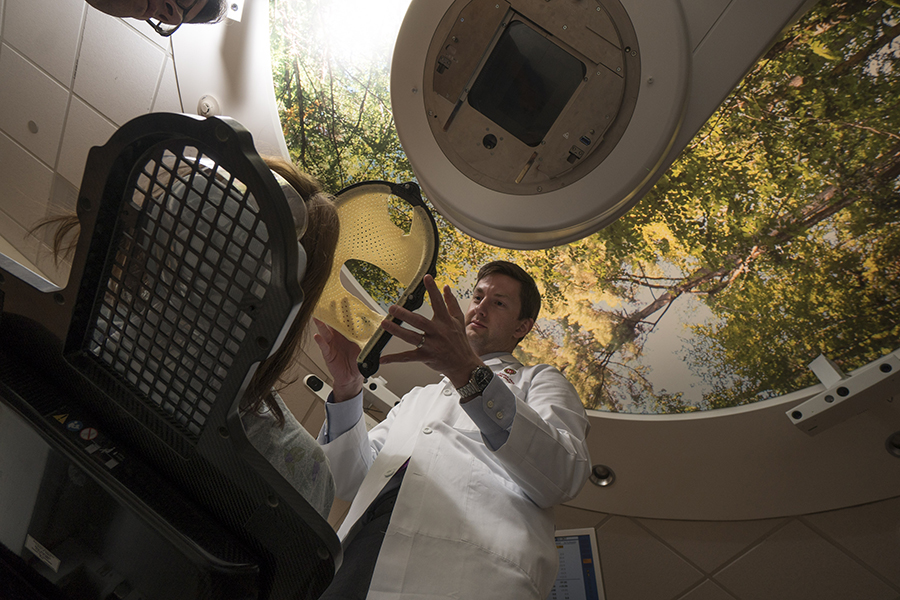 Dr. Zac Labby, assistant professor in the Department of Human Oncology, assistant professor in the Department of Human Oncology, demonstrates placement of the plastic face mask used for frameless stereotactic radiosurgery