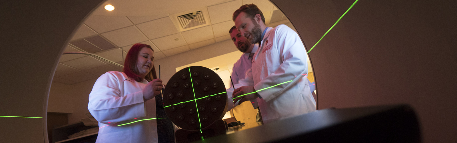 Medical Physics Residents and faculty adjusting LINAC