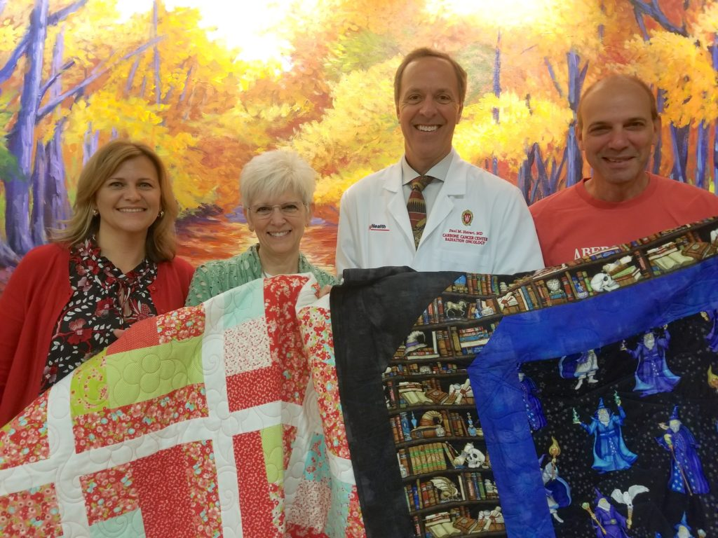 Janet Nanni, Denise Wright, Dr. Paul Harari and Peter Nanni display a couple of quilts donated to UW Radiation Oncology Clinic