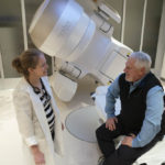 Dr. Jessica Schuster and patient Brad Glassel in front of the Varian TrueBeam Radiotherapy System at UW Cancer Clinic Johnson Creek